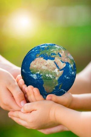 Photo pour Enfants tenant la planète 3D entre les mains sur fond de printemps vert. Jour de la Terre concept de vacances. Éléments de cette image fournis par la NASA - image libre de droit