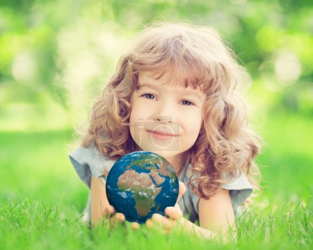 Photo for Child holding 3D planet in hands against green spring background. Earth day holiday concept. Elements of this image furnished by NASA - Royalty Free Image