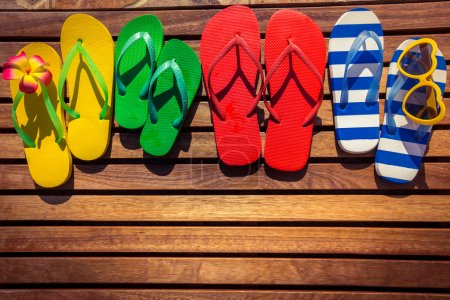 Photo for Multicolor flip-flops on wooden background. Summer family vacation concept - Royalty Free Image