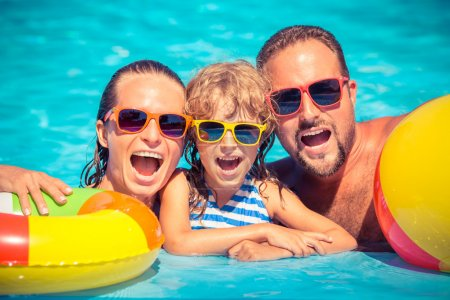Photo for Happy family playing in swimming pool. Summer vacation concept - Royalty Free Image