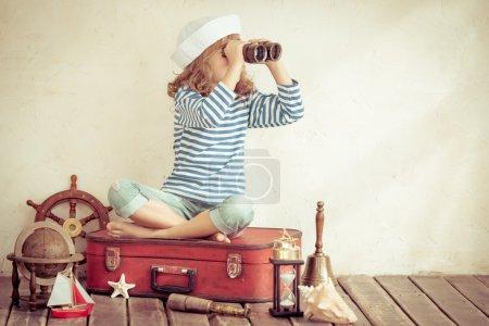 Photo pour Fille regardant à travers les jumelles, Joyeux enfant jouant avec des choses nautiques vintage. Le gamin s'amuse à la maison. Rêve marin d'été et imagination. Concept d'aventure et de voyage. Image tonique rétro - image libre de droit