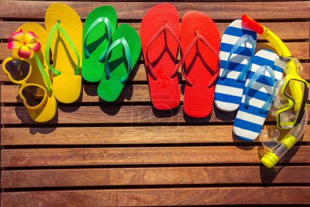 Multicolor flip-flops on wooden background.