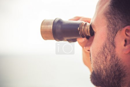 Man looking through the binoculars