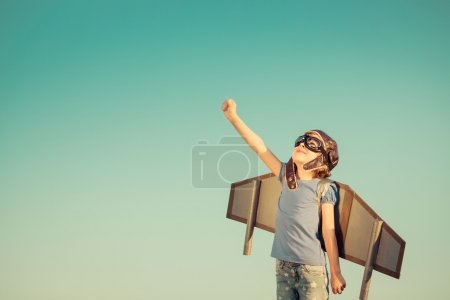 Photo for Happy child playing with toy wings against summer sky background. Retro toned - Royalty Free Image