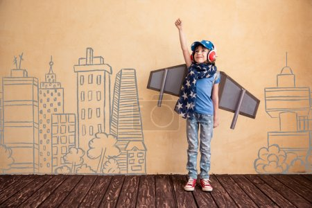 Photo for Happy child playing at home. Kid having fun with toy paper wings - Royalty Free Image