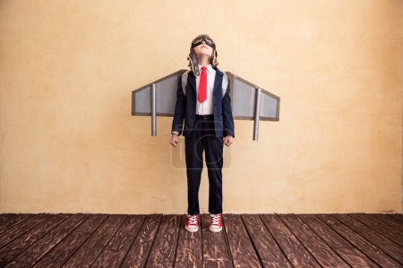young businessman with toy paper wings