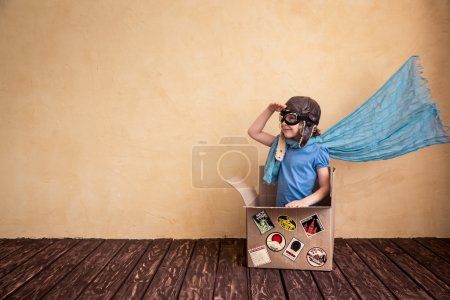 Happy child playing in cardboard box. Kid having f...