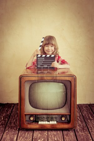 Photo for Funny kid holding clapper board. Retro TV. Cinema concept - Royalty Free Image