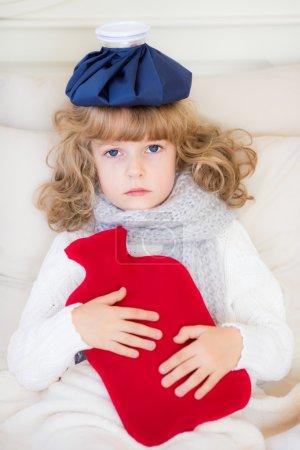 Photo pour Enfant malade avec fièvre et bouillotte à la maison - image libre de droit