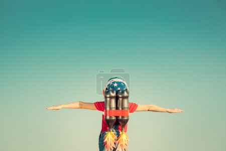 Photo for Kid with jet pack against autumn sky background. Child playing outdoors. Success, leader and winner concept. Retro toned - Royalty Free Image