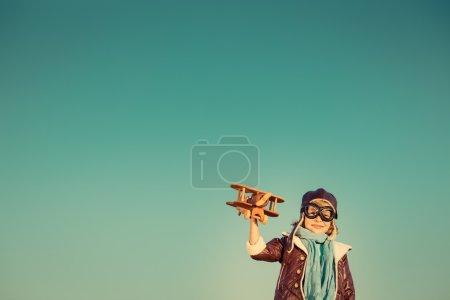 Photo pour Pilote enfant avec jouet avion en bois sur fond de ciel d'automne. Rétro tonique - image libre de droit