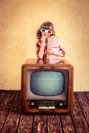 Photo for Child playing at home. Funny kid eating popcorn on retro TV. Cinema concept - Royalty Free Image