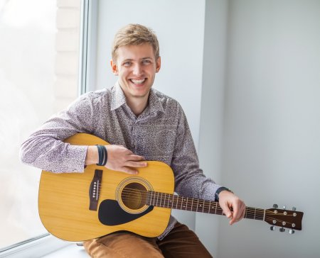 Photo for Portrait of handsome smiling man with guitar sitting on floo - Royalty Free Image