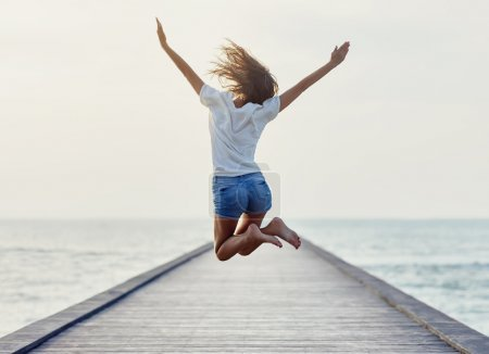 Photo for Back view of jumping girl on the pier. Freedom concept - Royalty Free Image