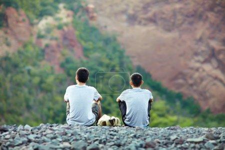 Foto de Dos jóvenes turistas sentados en un acantilado rocoso y disfrutando de una hermosa vista - Imagen libre de derechos