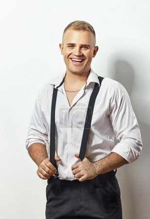 young man in white shirt and suspenders