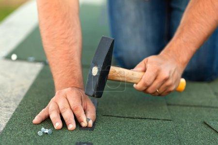 Worker hands installing bitumen roof shingles - horizontal crop