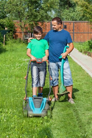 Father and son mowing the lawn