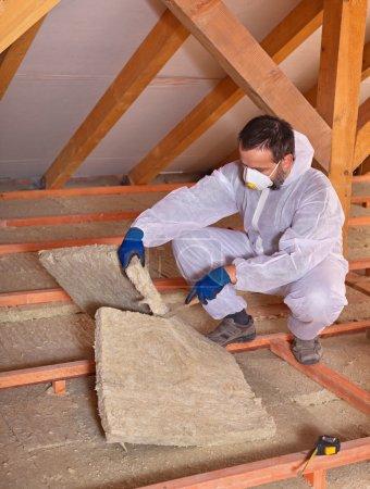 Foto de Panel de lana mineral de corte trabajador que instala aislamiento térmico en un edificio - Imagen libre de derechos