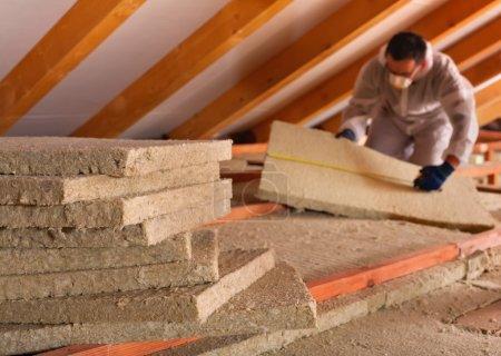 Foto de Aislamiento térmico de un edificio - paneles de lana mineral se apilan con el hombre midiendo en el fondo - Imagen libre de derechos