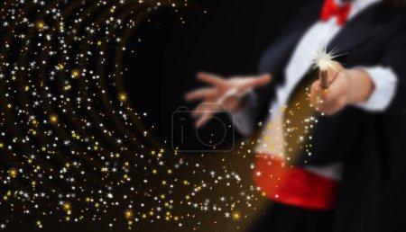 Foto de Manos del mago con varita mágica evocación brillante secuencia de estrellas - copia espacio - Imagen libre de derechos