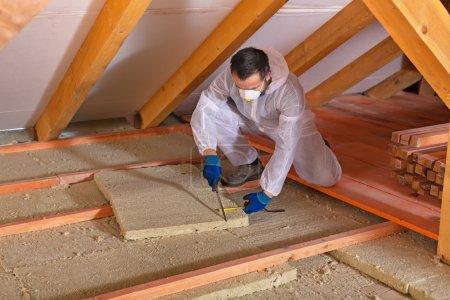 Foto de Hombre que pone capa de aislamiento térmico bajo el techo utilizando paneles de lana mineral - Imagen libre de derechos