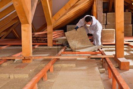 Foto de Hombre instalando capa de aislamiento térmico bajo el techo - utilizando paneles de lana mineral - Imagen libre de derechos