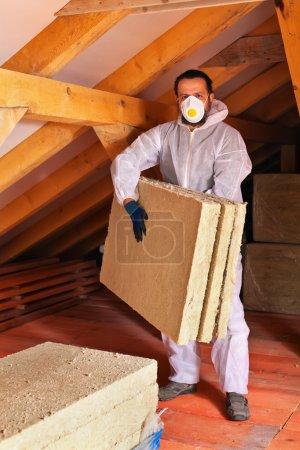 Foto de Hombre que pone capa de aislamiento térmico bajo el techo - llevar los paneles de lana mineral - Imagen libre de derechos