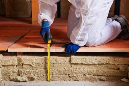 Foto de Medición del espesor del aislamiento térmico - manos de los trabajadores con cinta métrica - Imagen libre de derechos