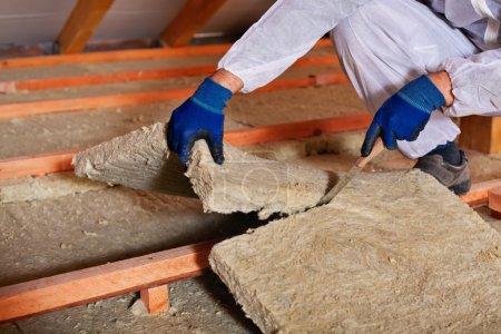 Foto de Instalación de capa de aislamiento térmico - primer plano en las manos de corte de lana de roca - Imagen libre de derechos