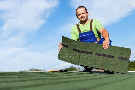 Photo pour Homme installant des bardeaux de toit de bitume - retenant quelques morceaux - image libre de droit