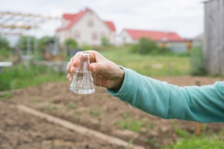 Photo pour Main féminine avec éprouvette et plante. Engrais en verrerie de laboratoire . - image libre de droit