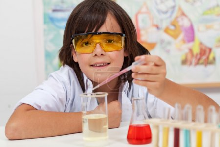 Photo for Young pupil conducting a simple chemical experiment in elementary science class - Royalty Free Image