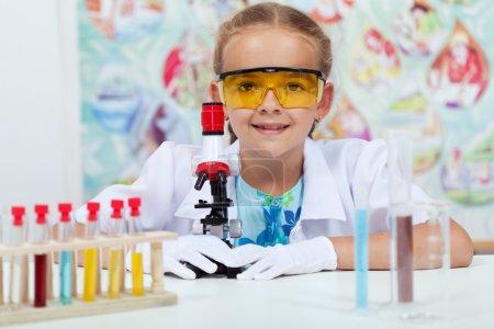 Photo pour Petite fille expérimentant en classe de science élémentaire - avec des gants et des lunettes de protection - image libre de droit