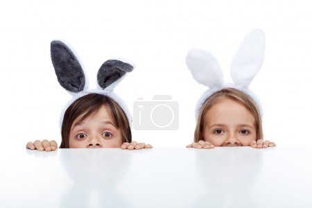 Photo pour Kids with bunny ears peeking from beneath the table - waiting for the easter rabbit - image libre de droit