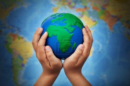 Photo pour Concept écologique avec globe terrestre entre les mains d'un enfant contre une carte floue du monde - image libre de droit
