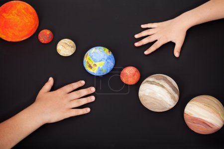 Kids hands with the planets of the solar system
