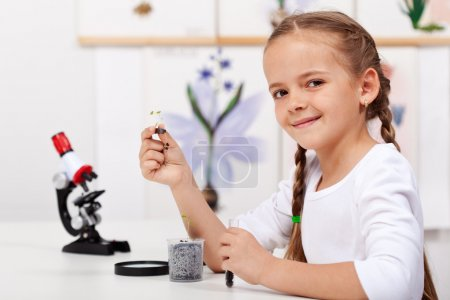 Young girl study plants in biology class