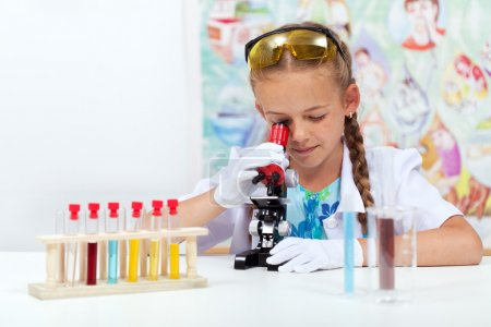Photo for Little girl in elementary school science class using microscope - Royalty Free Image