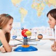 Kids with a scale model planetary system in geogra...