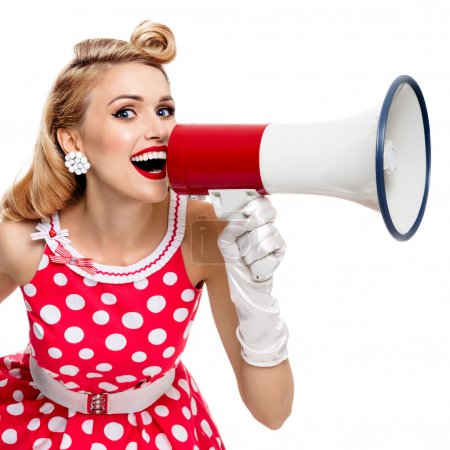 Photo for Portrait of woman holding megaphone, dressed in pin-up style red dress in polka dot and white gloves, isolated on white background. Caucasian blond model posing in retro fashion vintage studio shoot. - Royalty Free Image