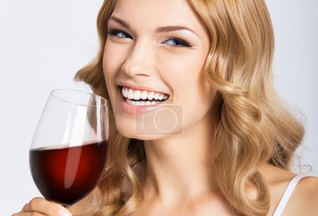 Young happy woman with glass of red wine, on gray