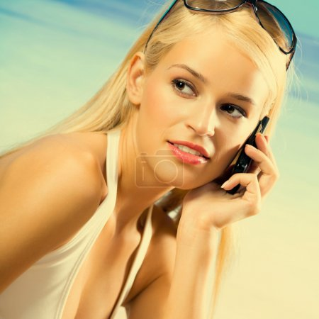 Young beautiful woman with cellphone on beach