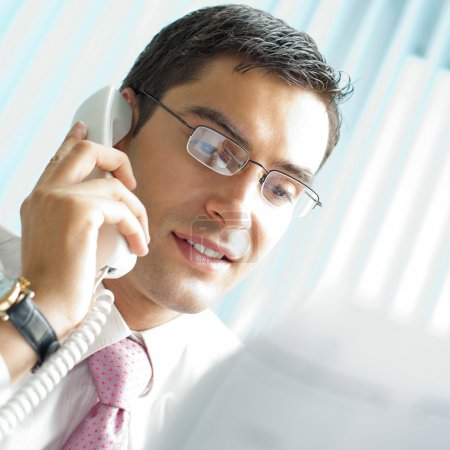 Businessman with phone and document at office