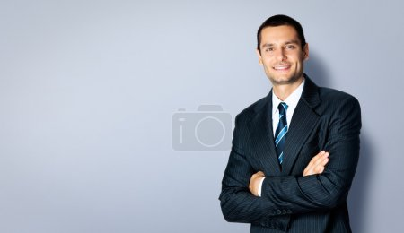 Photo for Happy smiling businessman with crossed arms pose, with blank copyspace area for text or slogan, against grey background - Royalty Free Image
