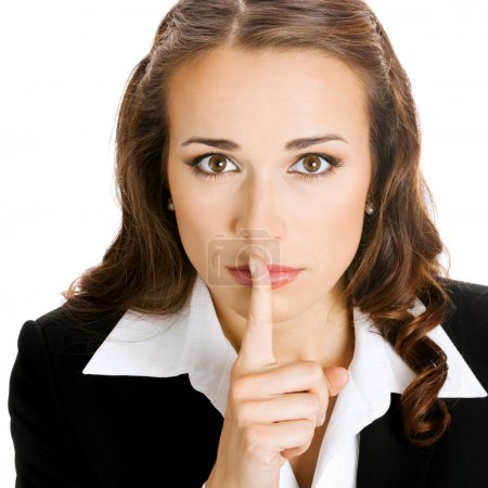 Portrait of young serious businesswoman keeping finger on her lips and asking to keep quiet, isolated