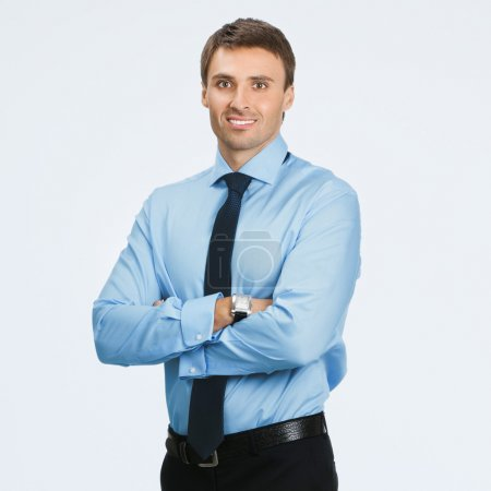 Photo for Portrait of young happy smiling business man, over grey background - Royalty Free Image