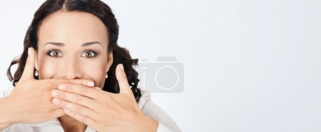 Business woman covering mouth, on grey