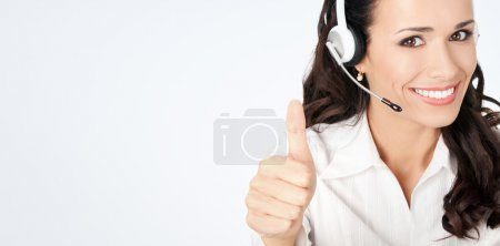 Photo for Portrait of happy smiling cheerful customer support phone operator in headset showing thumbs up gesture, against grey background, with copyspace - Royalty Free Image