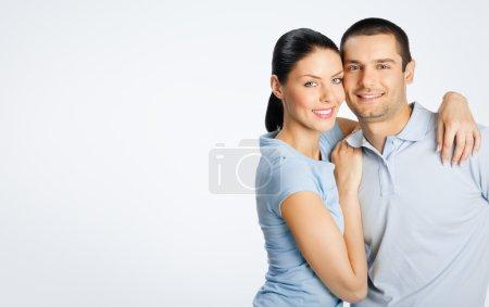 Photo pour Portrait de joyeux jeune couple charmant, avec espace de copie vide pour le texte ou le slogan, sur fond gris - image libre de droit